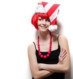Mujer joven que desgasta el sombrero de Santas. Foto de archivo