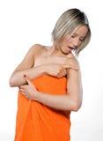 Mujer joven que desgasta la toalla anaranjada que controla su topo Imagen de archivo libre de regalías