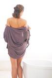 Mujer joven que desnuda en cuarto de baño Visión trasera Foto de archivo libre de regalías