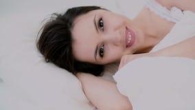 Mujer joven que despierta en cama La muchacha mira a la cámara y a las sonrisas lindas Mujer feliz por mañana que liga con alguie almacen de video