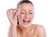 Mujer joven que despluma sus cejas con las pinzas imagenes de archivo