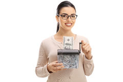 Mujer joven que destruye un billete de banco del dólar en una trituradora de papel Foto de archivo libre de regalías