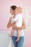 Mujer joven que detiene al bebé lindo y que mira lejos Imagen de archivo