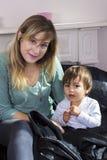 Mujer joven que detiene al hijo en los brazos fotografía de archivo libre de regalías
