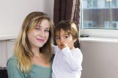 Mujer joven que detiene al hijo en los brazos imagenes de archivo