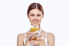 Mujer joven que detiene el zumo de naranja y a la cinta métrica en un fondo ligero, dieta Imágenes de archivo libres de regalías