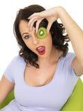 Mujer joven que detiene a Kiwi Fruit cortado maduro fresco sobre ojo Foto de archivo