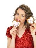Mujer joven que detiene a las tarjetas del día de San Valentín Ginger Biscuits Imagen de archivo
