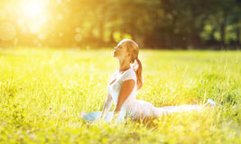 Mujer joven que disfruta de aptitud y de yoga en hierba verde en verano Imagenes de archivo
