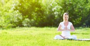 Mujer joven que disfruta de la meditación y de la yoga en hierba verde en summe imagen de archivo