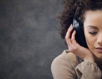 Mujer joven que disfruta de música Fotos de archivo libres de regalías