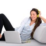 Mujer joven que disfruta de música con la computadora portátil Fotos de archivo libres de regalías