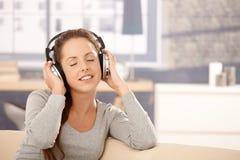 Mujer joven que disfruta de música a través de los auriculares Fotos de archivo