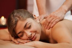 Mujer joven que disfruta de masaje profesional fotografía de archivo