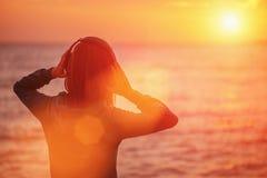 Mujer joven que disfruta de puesta del sol hermosa sobre el mar Foto de archivo