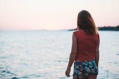 Mujer joven que disfruta de puesta del sol por el mar Imagen de archivo libre de regalías