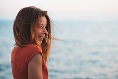 Mujer joven que disfruta de puesta del sol por el mar Fotos de archivo