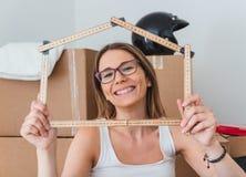 Mujer joven que disfruta de su nuevo hogar imagenes de archivo