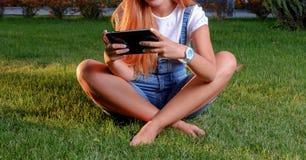 Mujer joven que disfruta de su tiempo en parque con la tableta Foto de archivo libre de regalías