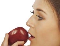 Mujer joven que disfruta de un pedazo de manzana roja Fotografía de archivo