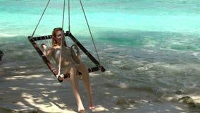 Mujer joven que disfruta de un resto en la hamaca en la playa al sonido de la resaca almacen de video