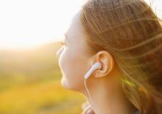 Mujer joven que disfruta de una música en la temporada de otoño imagen de archivo libre de regalías
