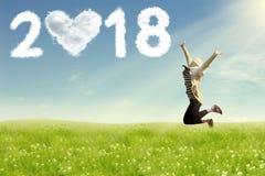 Mujer joven que disfruta del Año Nuevo que salta en campo Foto de archivo