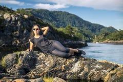 Mujer joven que disfruta del día soleado en las rocas al lado del fjor Fotografía de archivo