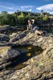 Mujer joven que disfruta del día soleado en las rocas al lado del fjor Fotos de archivo libres de regalías