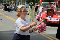 Mujer joven que distribuye las banderas en desfile del 4 de julio, Saratoga Springs, Ny, 2013 Foto de archivo