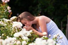 Mujer joven que dobla sobre rosas Imagenes de archivo