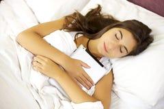 Mujer joven que duerme abrazando la tablilla en cama Imagen de archivo