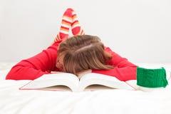 Mujer joven que duerme con el libro y la taza de café Imágenes de archivo libres de regalías