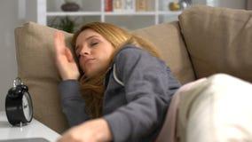 Mujer joven que duerme con el ordenador portátil en el sofá en casa metrajes