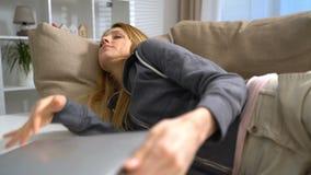 Mujer joven que duerme con el ordenador portátil en el sofá en casa, tiro del carro almacen de metraje de vídeo