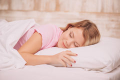 Mujer joven que duerme en cama Fotos de archivo