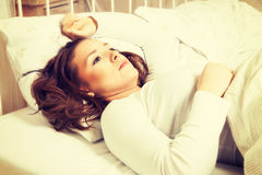 Mujer joven que duerme en cama Foto de archivo libre de regalías
