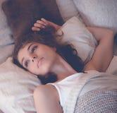 Mujer joven que duerme en cama Imágenes de archivo libres de regalías