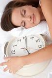 Mujer joven que duerme en cama con el reloj de alarma Foto de archivo