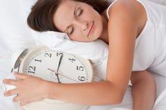 Mujer joven que duerme en cama con el reloj de alarma Imágenes de archivo libres de regalías