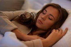 Mujer joven que duerme en cama en casa Imagen de archivo libre de regalías