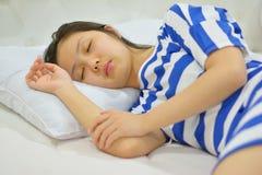 Mujer joven que duerme en cama en dormitorio Foto de archivo