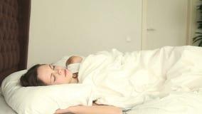 Mujer joven que duerme en cama incómoda almacen de metraje de vídeo
