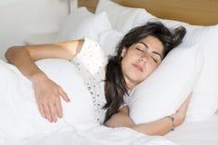 Mujer joven que duerme en cama por la mañana Fotos de archivo libres de regalías