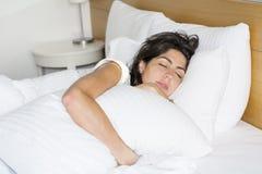 Mujer joven que duerme en cama por la mañana Fotografía de archivo libre de regalías