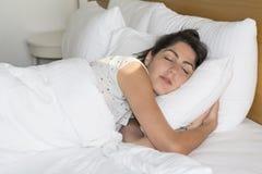 Mujer joven que duerme en cama por la mañana Foto de archivo libre de regalías