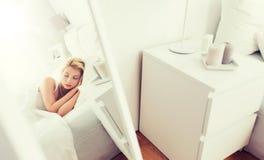Mujer joven que duerme en dormitorio de la cama en casa Foto de archivo libre de regalías