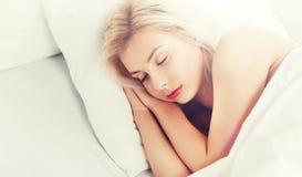 Mujer joven que duerme en dormitorio de la cama en casa Imágenes de archivo libres de regalías