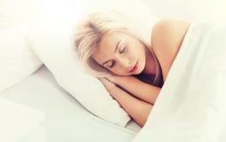 Mujer joven que duerme en dormitorio de la cama en casa Imagen de archivo libre de regalías