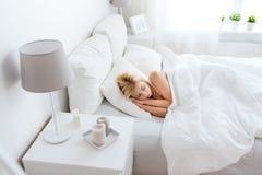 Mujer joven que duerme en dormitorio de la cama en casa Imagen de archivo